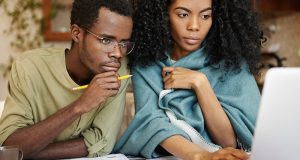 Young African wife and husband with many debts doing paperwork and tax returns together, analyzing expenses, planning family budget and calculating bills, sitting at kitchen table with laptop, calculator and papers